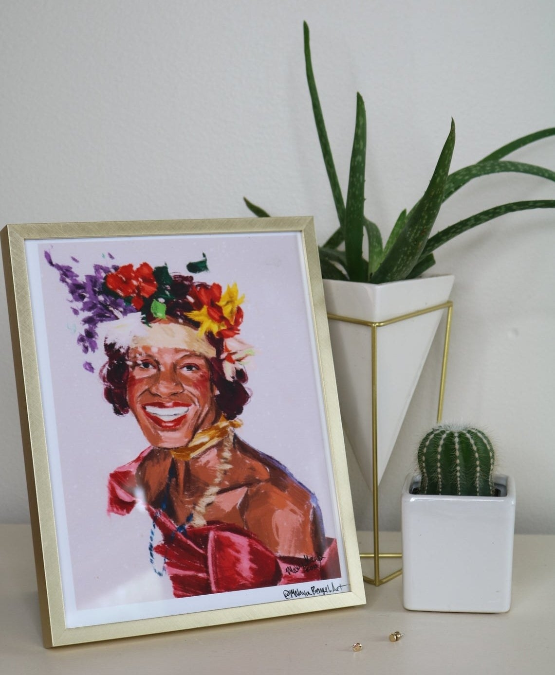 A colorful painted print of Marsha P. Johnson wearing an evening gown, flower crown, and showing off her dazzling smile