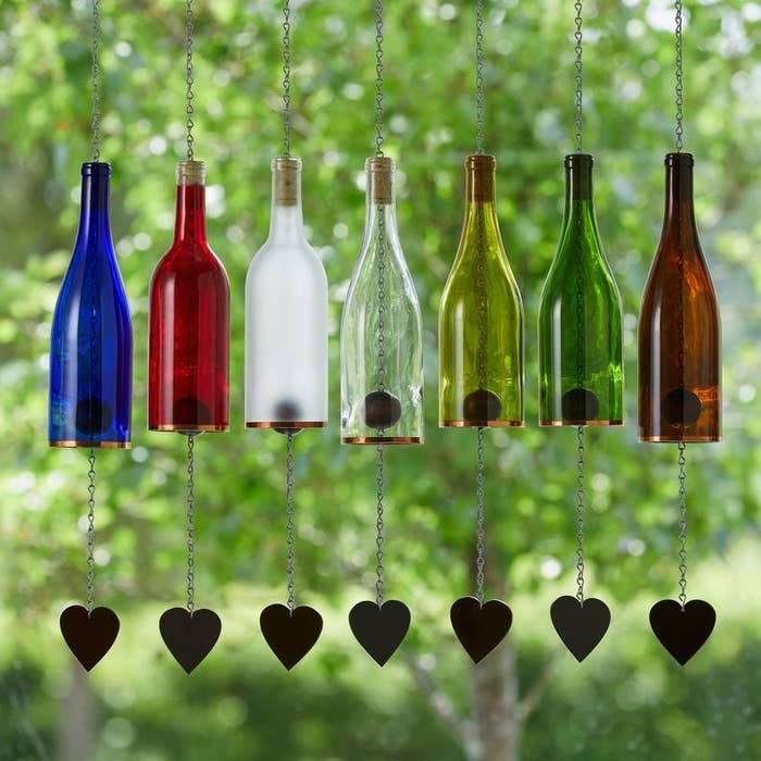 Seven wine bottles that have been transformed into wind chimes with hearts at the end of each chain