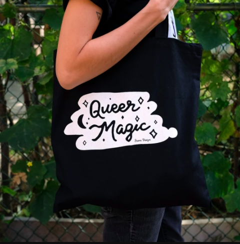 A black tote bag with an illustration on the front in white that says Queer Magic