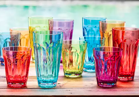 set of colorful drinking glasses in two sizes on an outdoor table