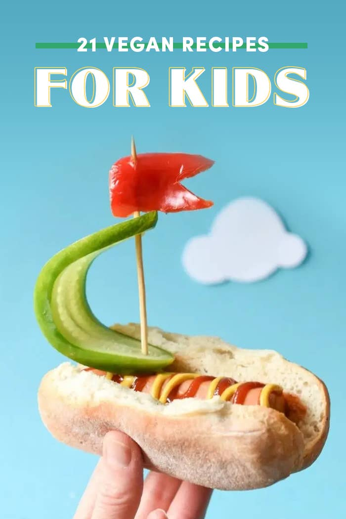 Hot dog that looks like a boat with a red pepper flag and cucumber as the sail.