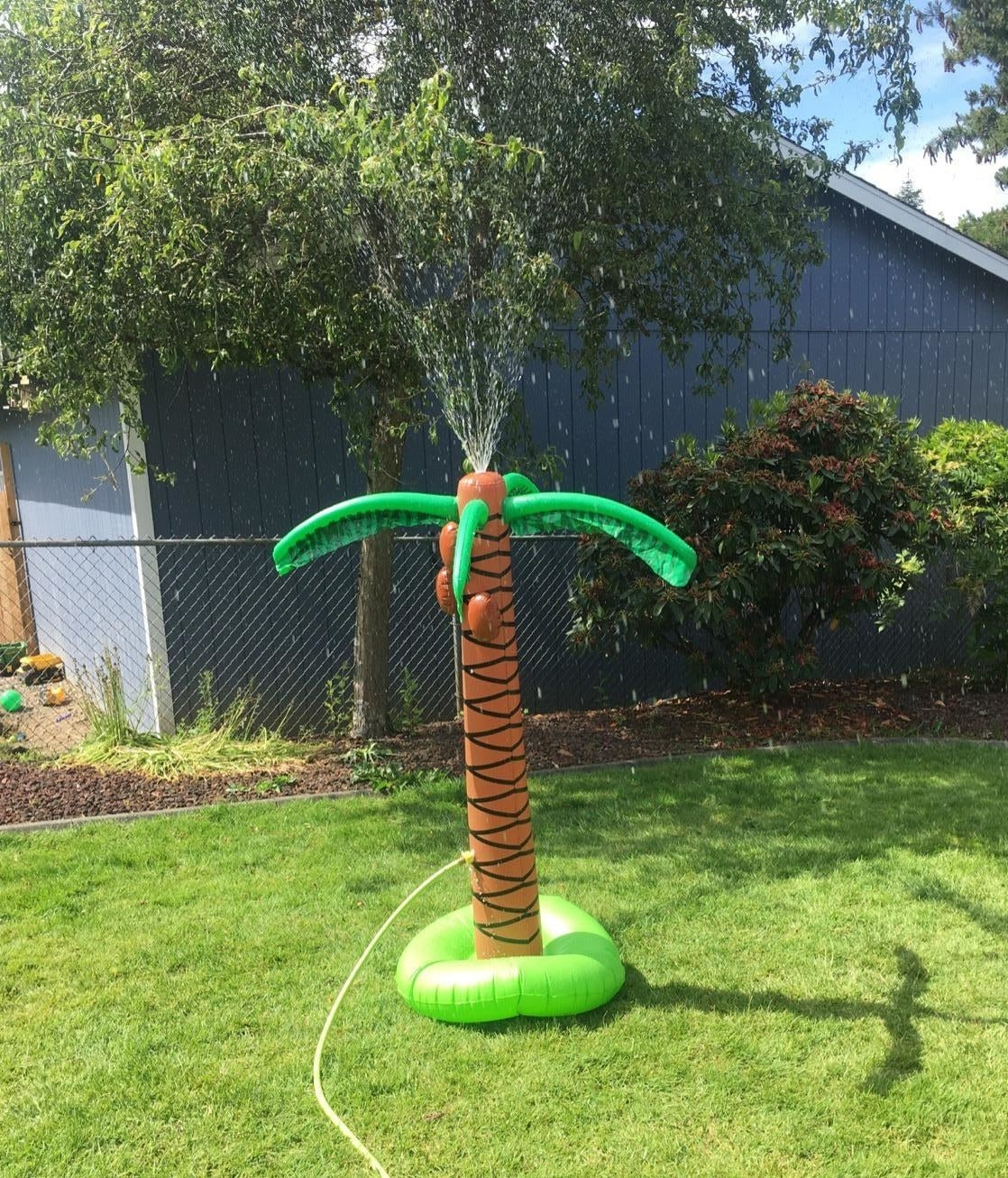inflatable palm tree with hose attached spraying water out its top