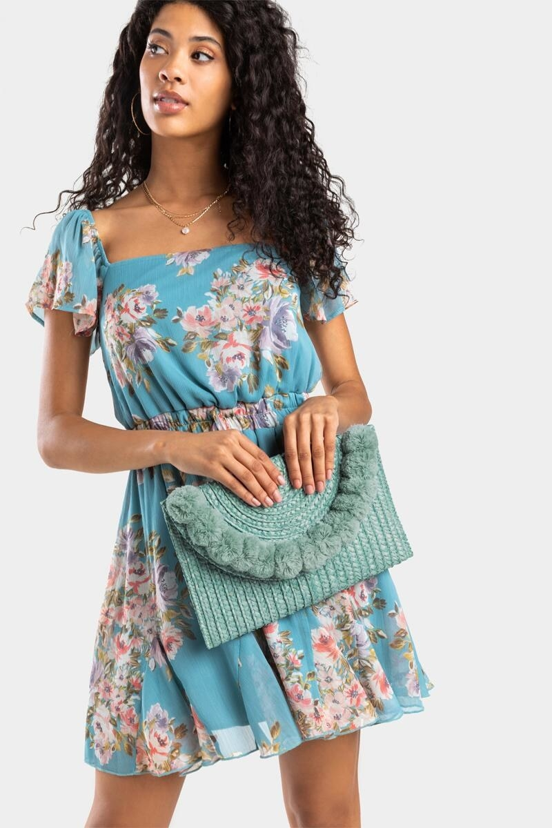 model holding the rectangle teal envelope style clutch with pom accent along the opening flap