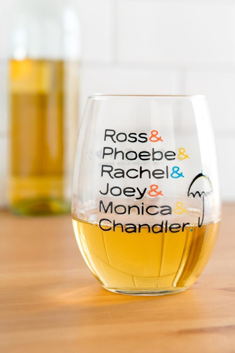 stemless wine glass with white wine in it that has a design of the Friends TV show character names