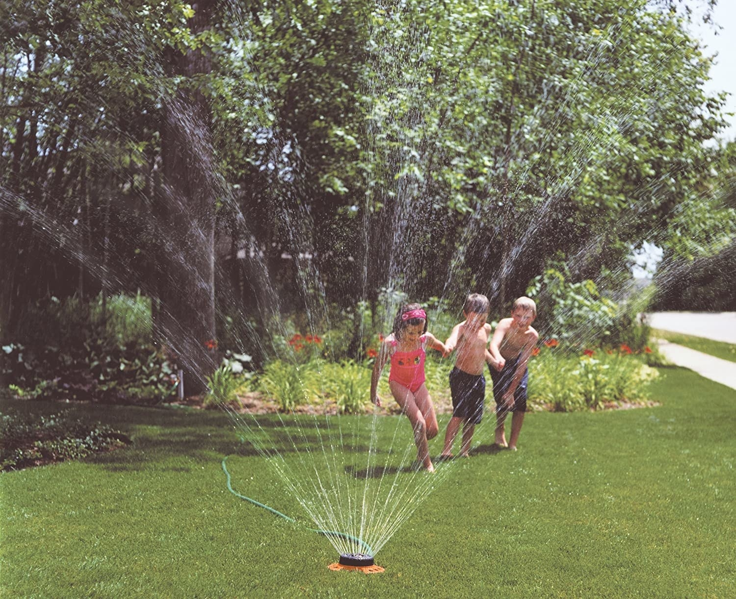 kids running through small round sprinkler spraying water in all directions