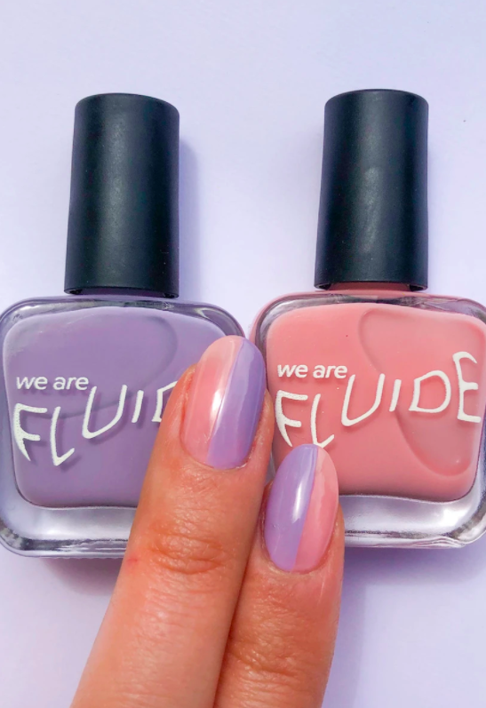 The lavender and pink shade of nail polish on a model's fingernails