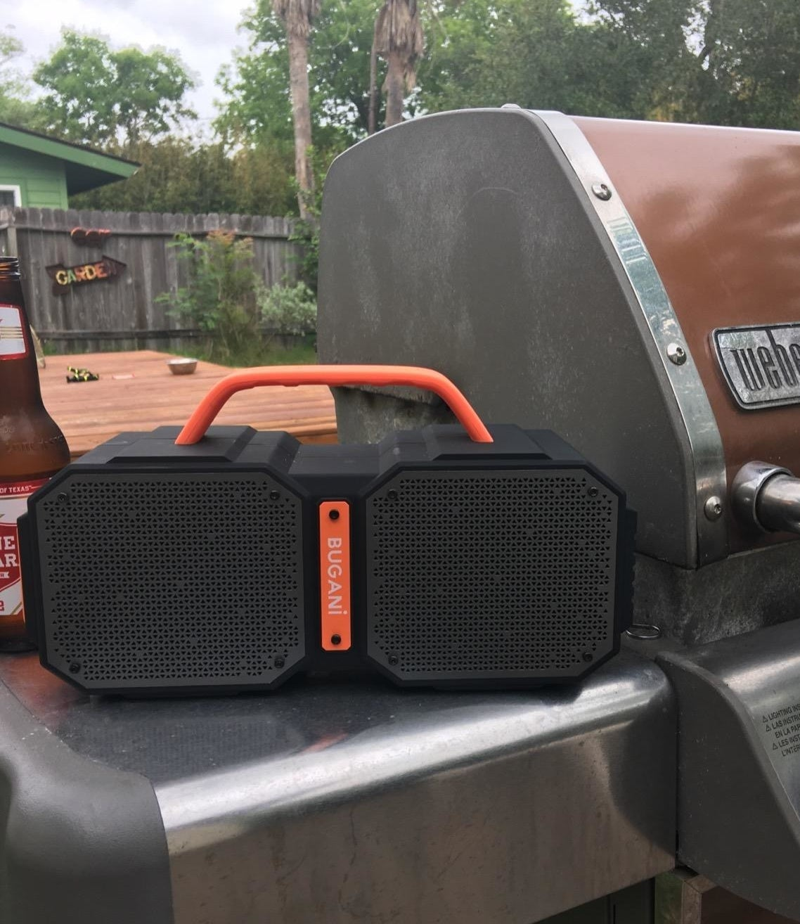 black and orange boombox-shaped speaker sitting on grill side table