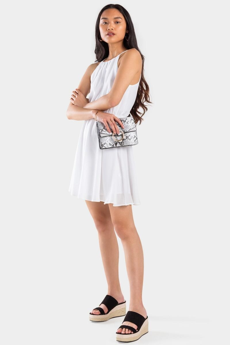 model wearing a white sleeveless dress with spaghetti straps, gathered waist, hits above the knee