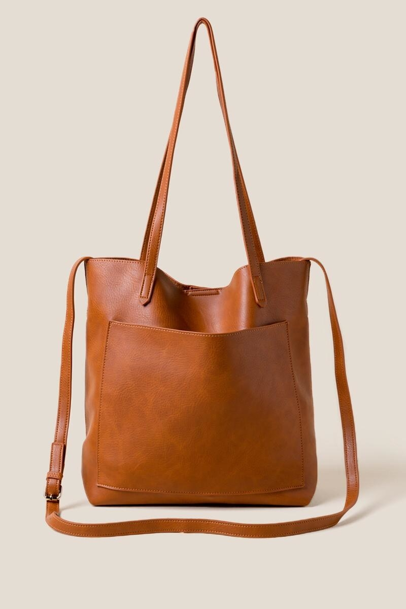 brown faux lather tote with a large pocket on the front, long shoulder straps, and a longer carrying strap