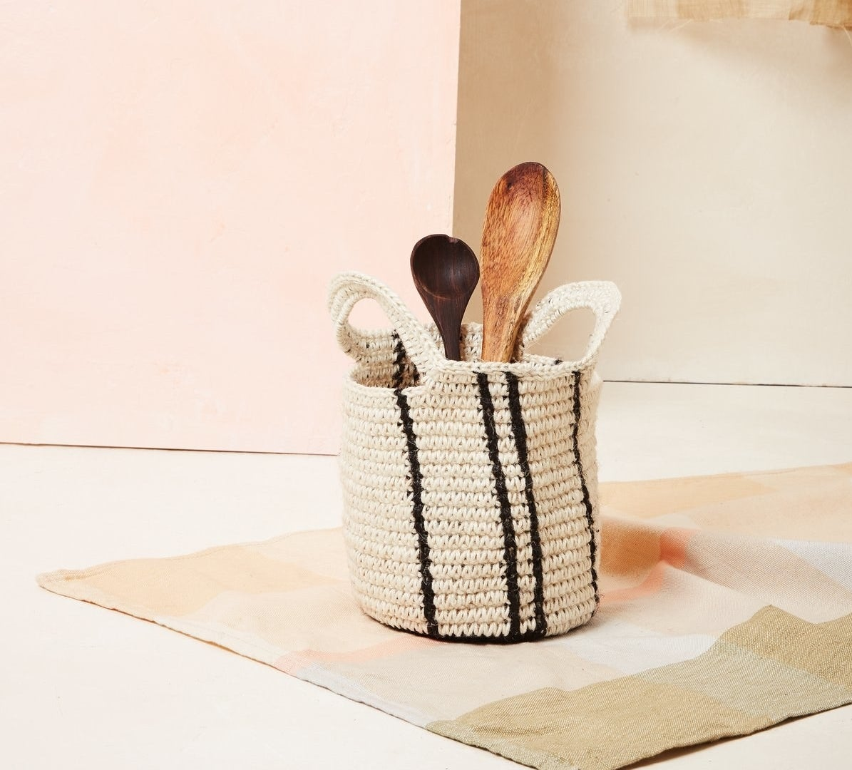 A small woven basket in white with small black vertical stripes with handles and kitchen utensils inside