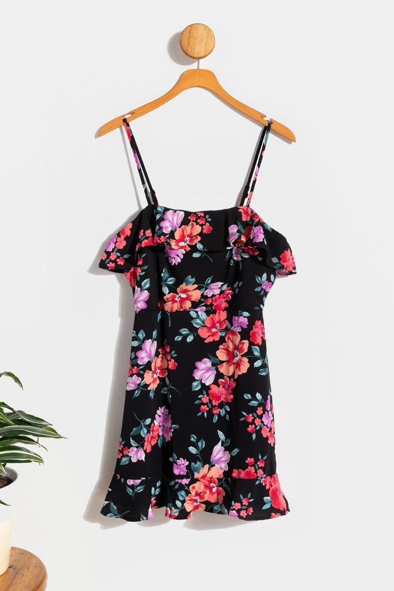 black with floral print dress hanging up on a wood coat hanger on a wall
