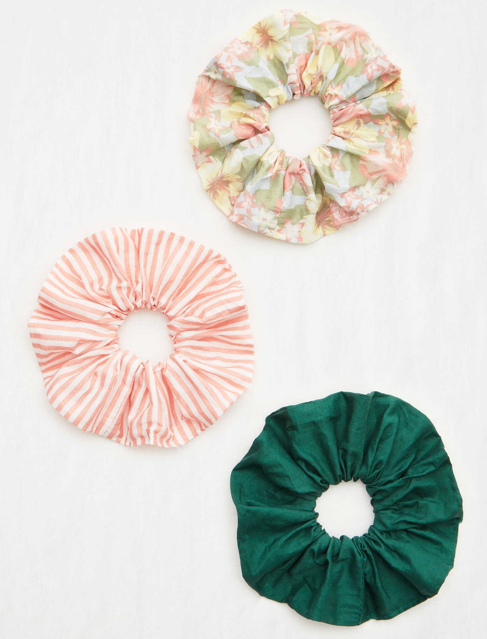 The three scrunchies: one floral print, one pinstriped light coral, one emerald