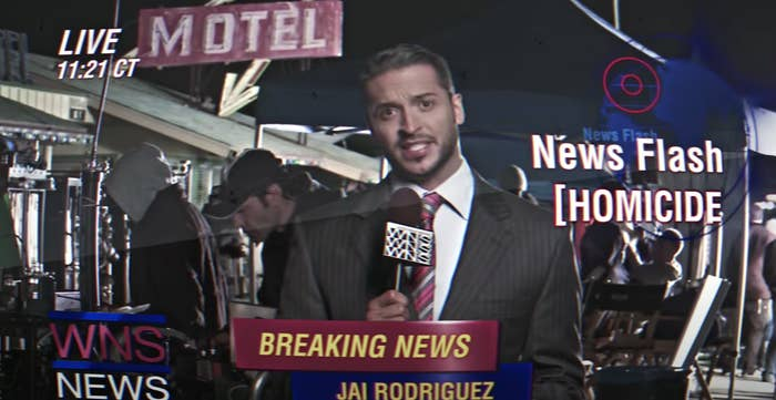Jai Rodriguez standing in front of a motel and giving a news broadcast