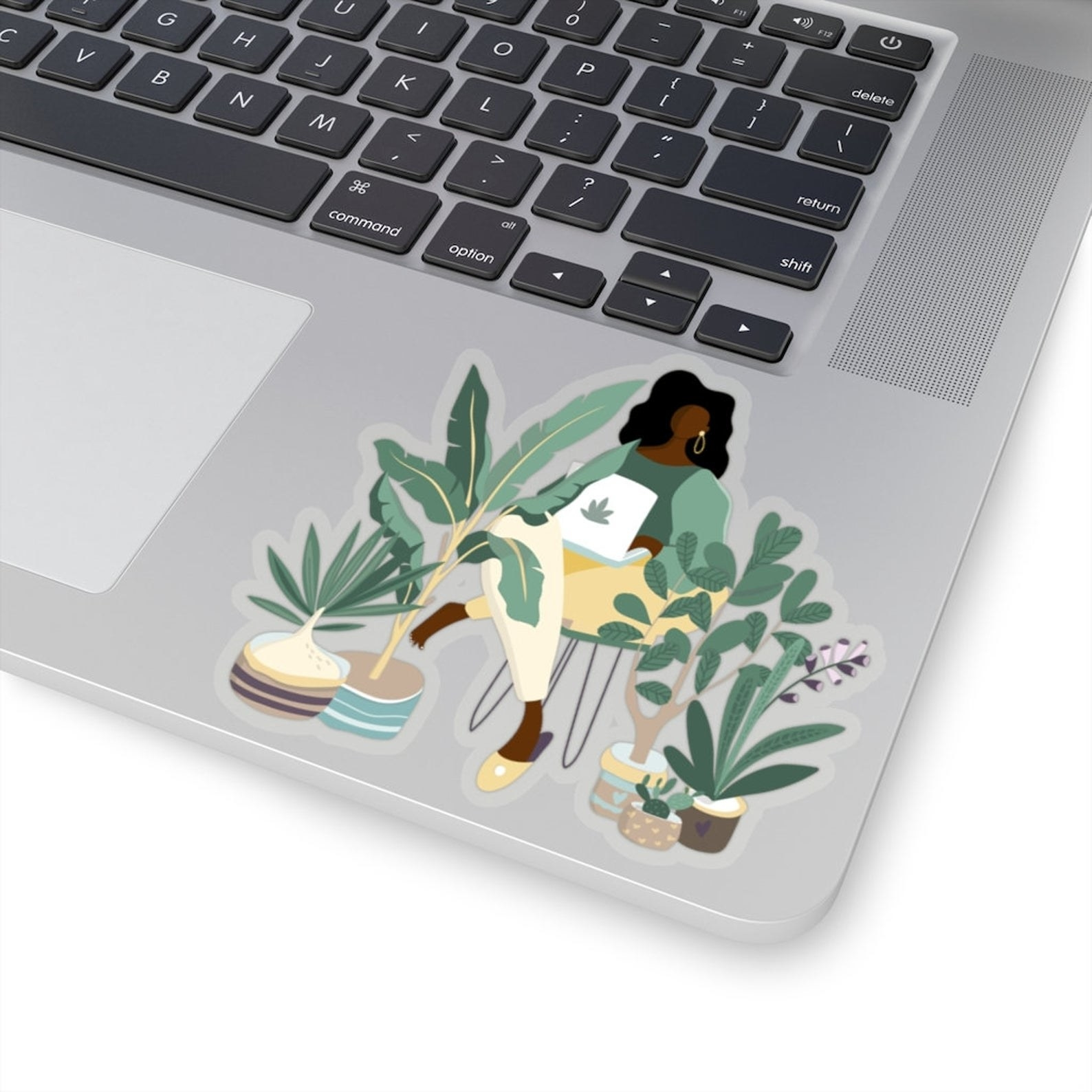A sticker that shows a woman sitting at a laptop with a plant sticker decal on it and other green plants of different sizes surrounding her.