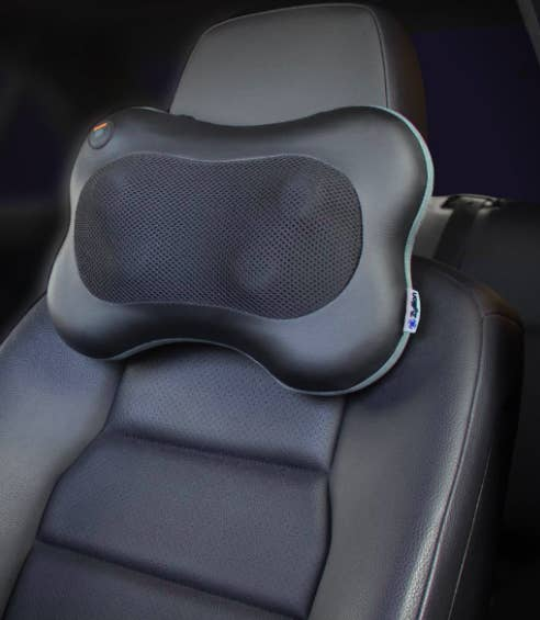 The massager attached just below the headrest of the driver's side car seat. It has four protruding massagers and heat-proof fabric in the center.