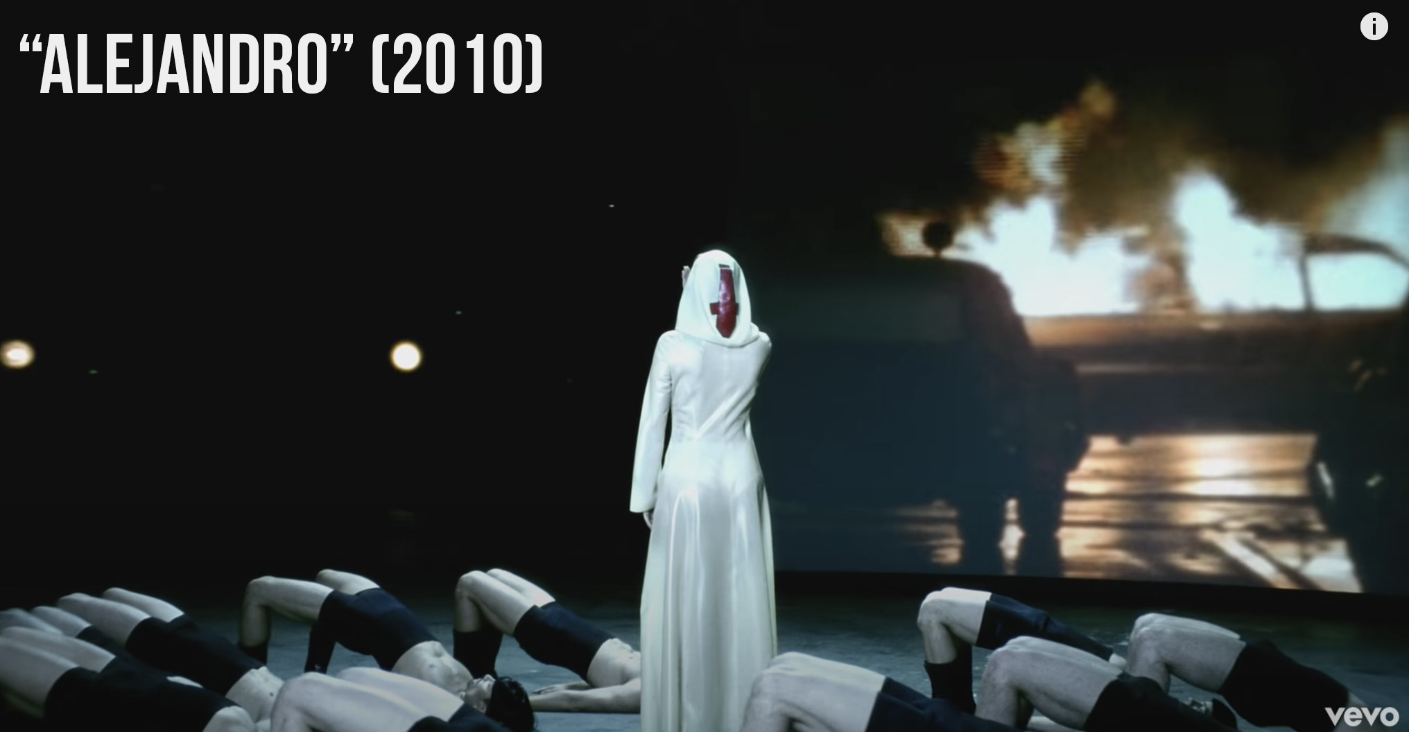 "Lady Gaga standing in front of a projection of some cars on fire in ""Alejandro"""