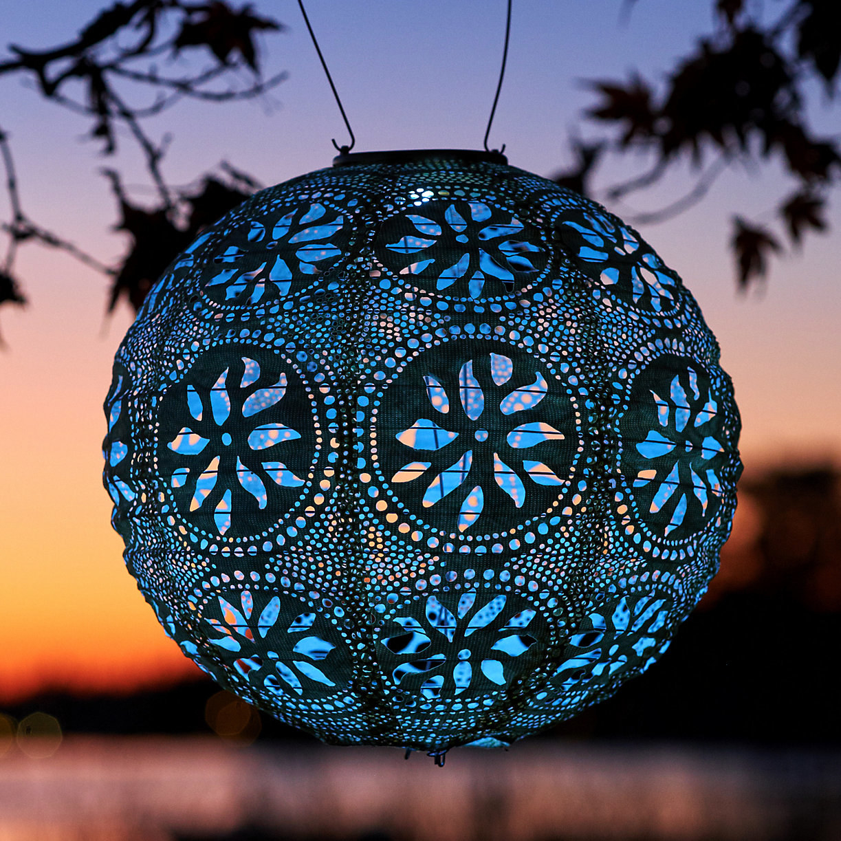 blue floral round lacy lantern hanging and illuminated