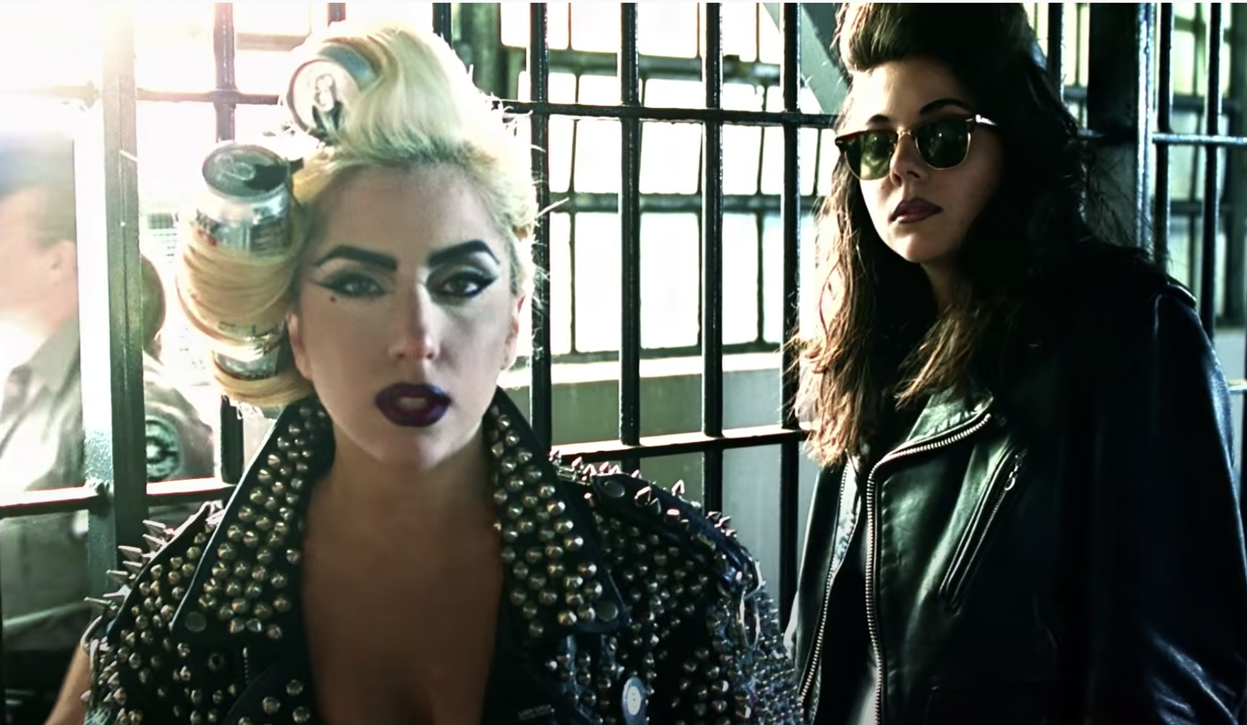 Lady Gaga looking at the camera from inside her prison cell while her sister stands behind her