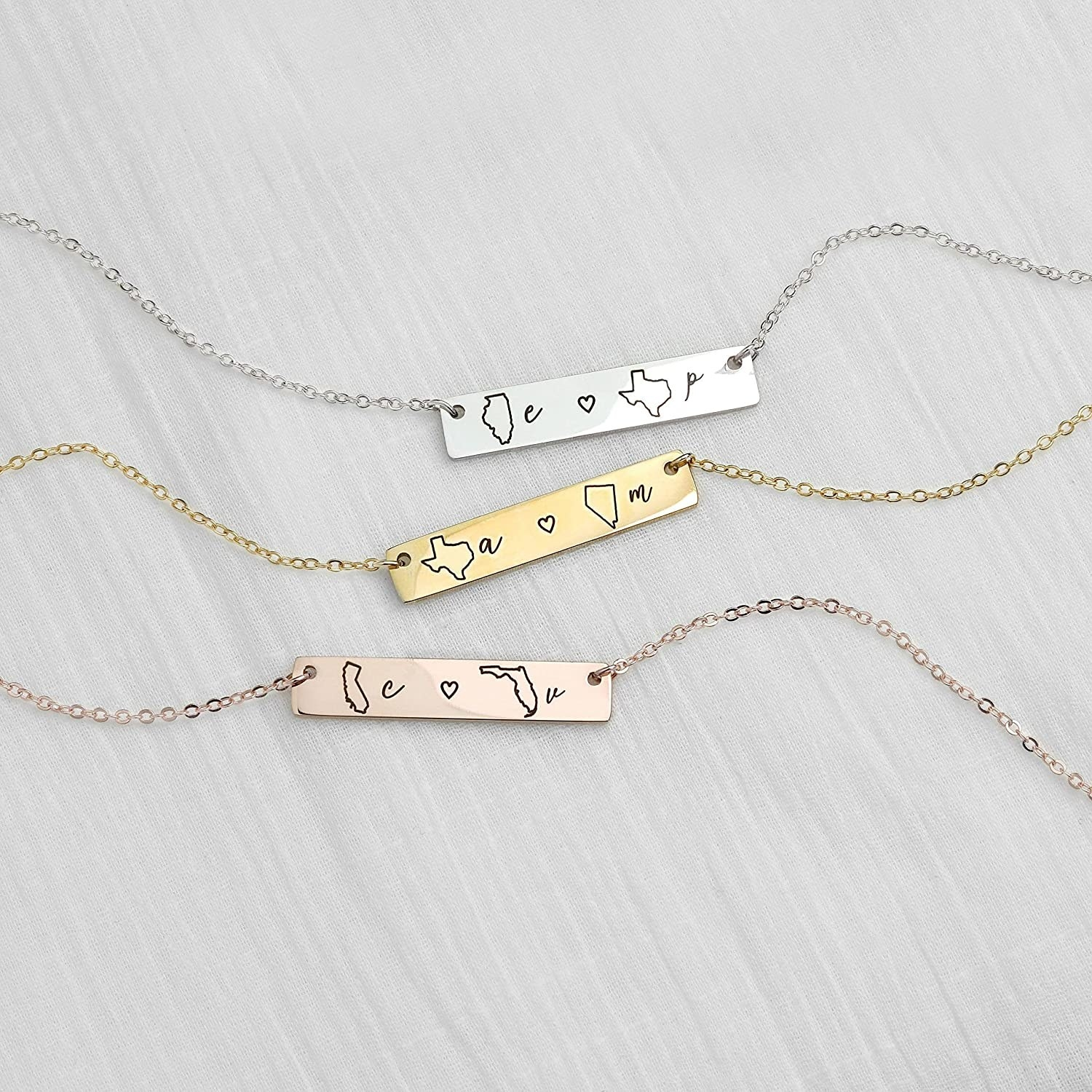 Necklaces in silver, gold, and rose gold with a bar that has different letters and state outlines on them