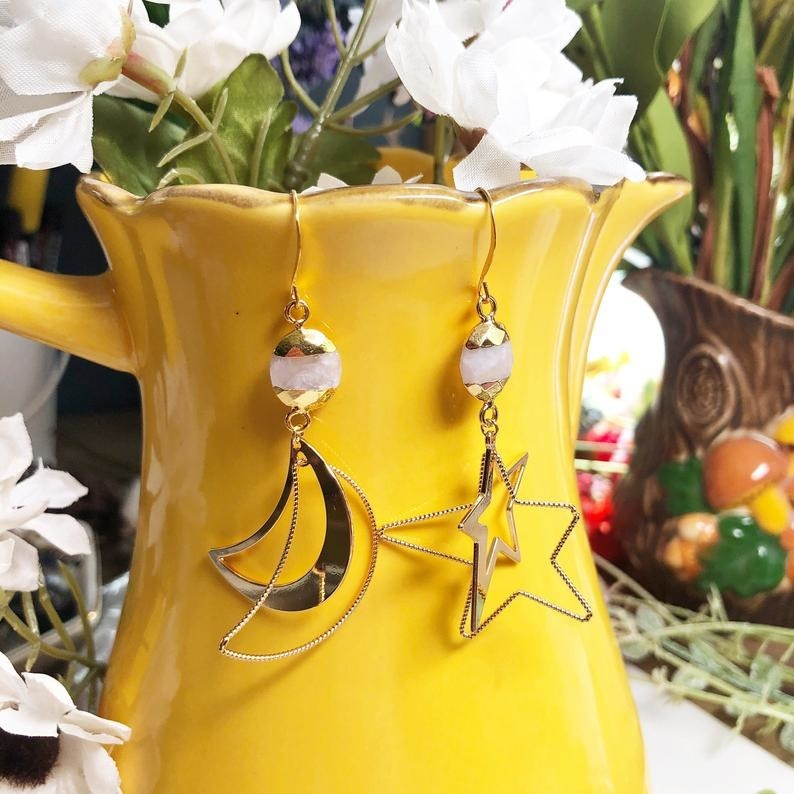The moon and star shaped earrings hanging on a yellow flower pot