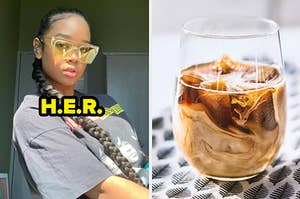H.E.R. wears a long braid and yellow-tinted sunglasses. She is sporting a black band tee shirt while sitting in a bedroom. Next to H.E.R. is an iced coffee in a wine glass, sitting on a leaf-patterned napkin.