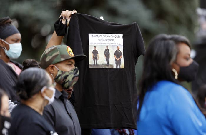 """Someone holds up a T-shirt that says """"#JusticeForElijahMcClain"""" in Denver, June 19."""