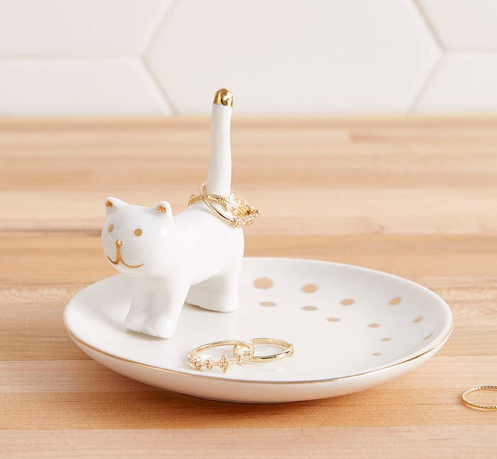 A smooth little saucer-like dish with a tiny cat figure on it