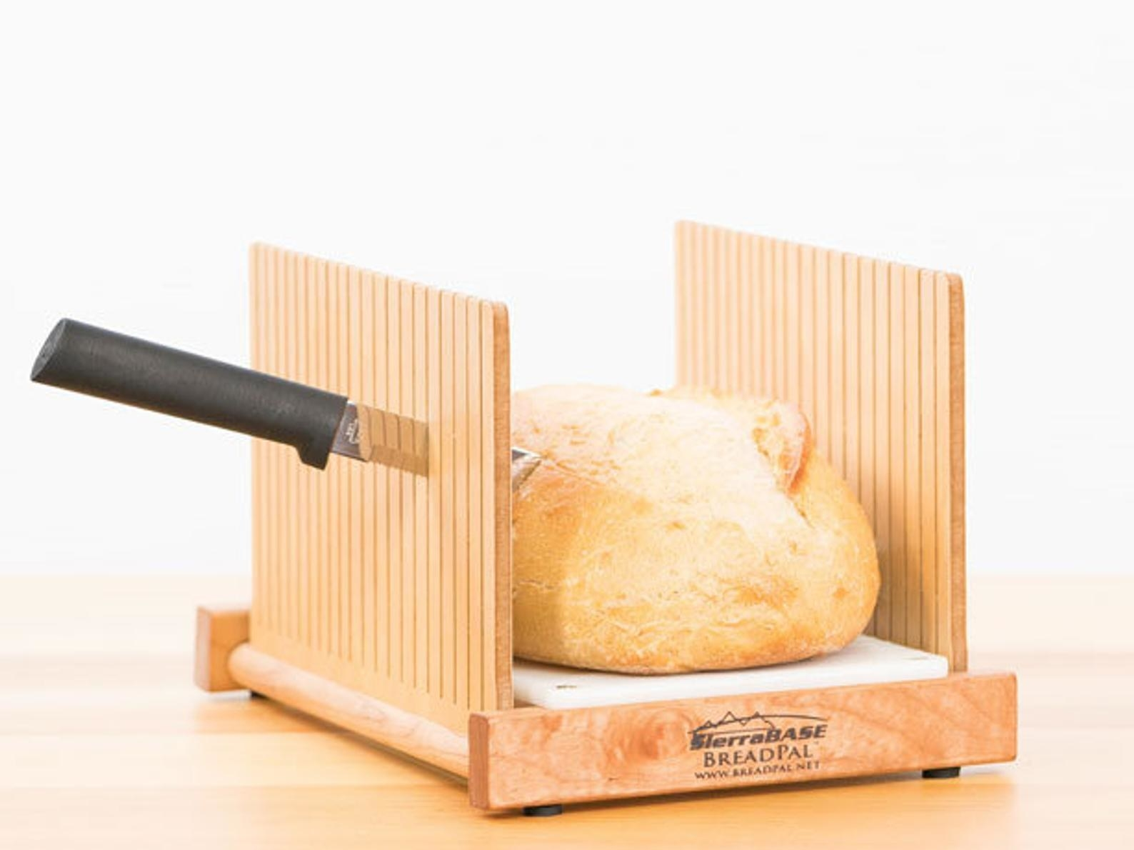 The wooden bread slicer, with a knife cutting between the slats and through the loaf