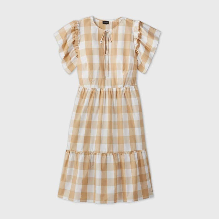 A tiered dress with flutter sleeves and a ribbon at the collar