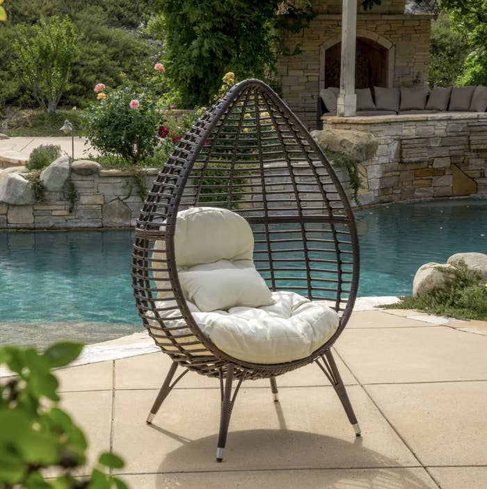 teardrop wicker chair with two tan fluffy pillows