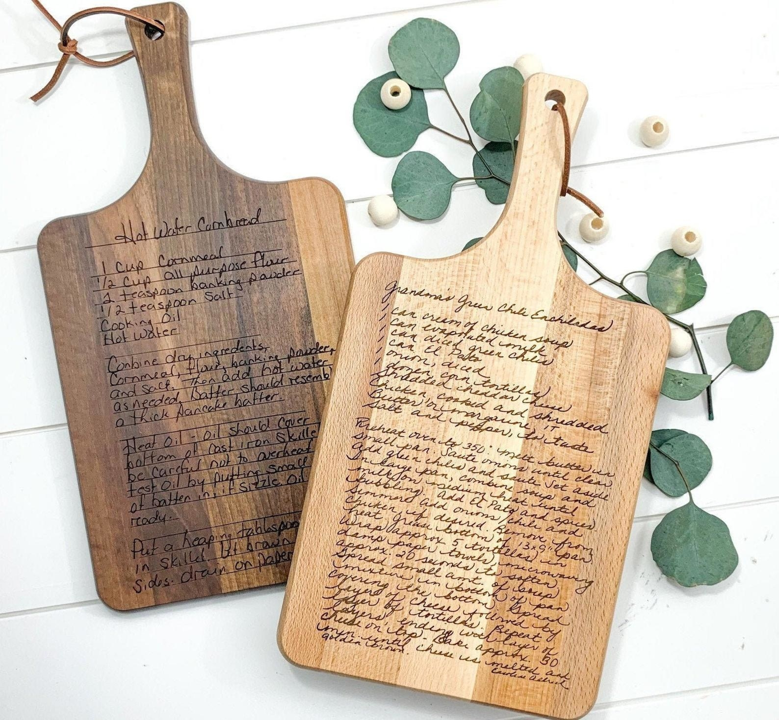 Two cutting boards in light and dark wood with different fonts of recipes engraved on them