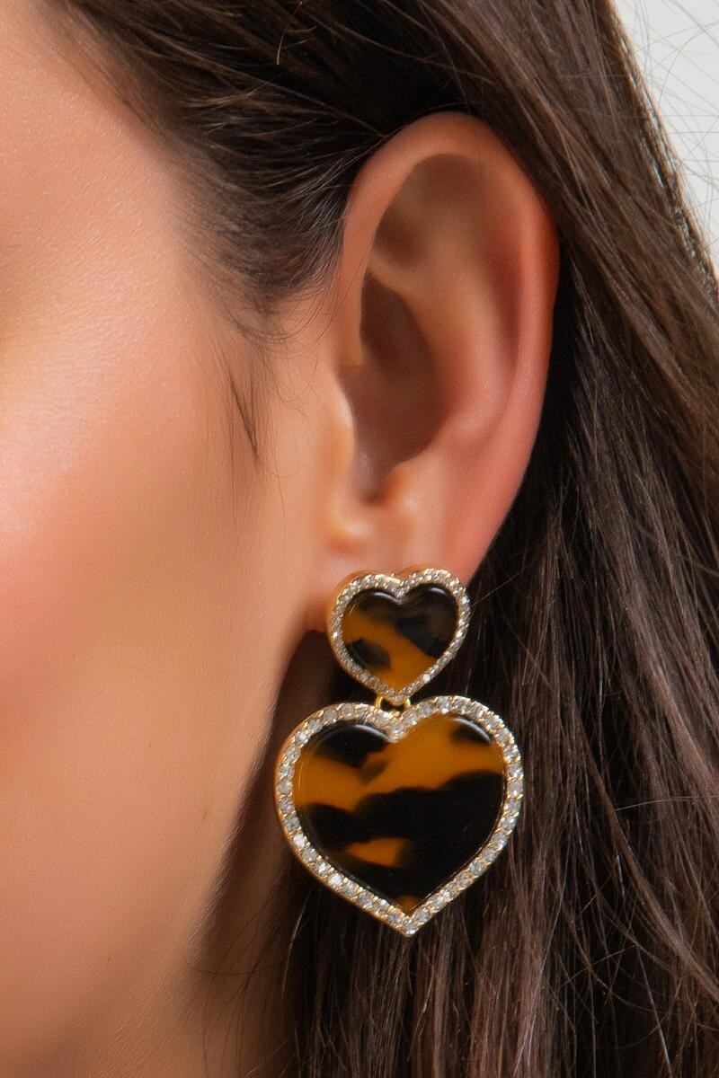 close up of model's ear with heart-shaped drop earrings that are in a tortoise shell pattern and have a sparkly perimeter