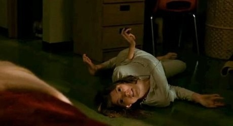 Actor Jennifer Carpenter laying with her body contorted on the floor as she's being possessed.
