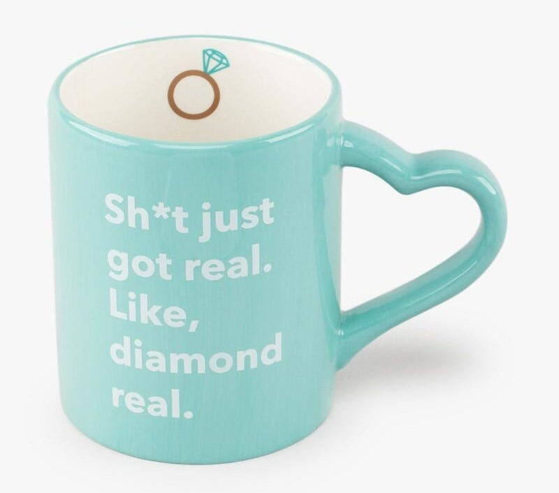 """light blue coffee with with heart-shaped handle, an engagement ring illustration inside the mug brim, and """"Sh*t just got real. Like, diamond real."""" on the outside"""
