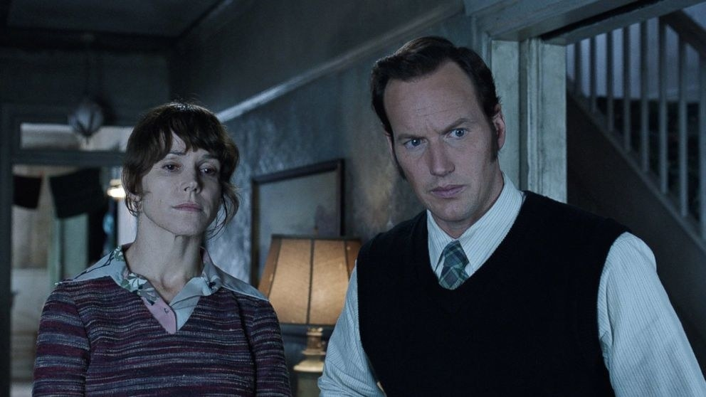 Actor Patrick Wilson looking concerned as he looks on at a haunted house.