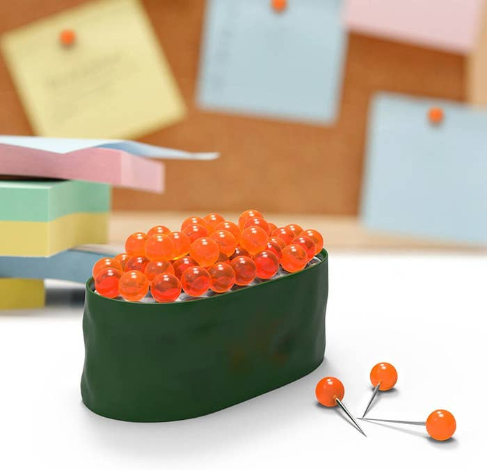 A piece of sushi with pins that look like roe