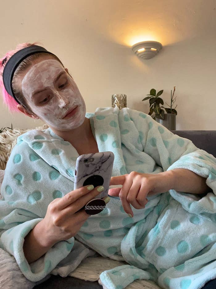 Me sitting on the couch in a robe, with a clay mask on my face, scrolling on my phone.