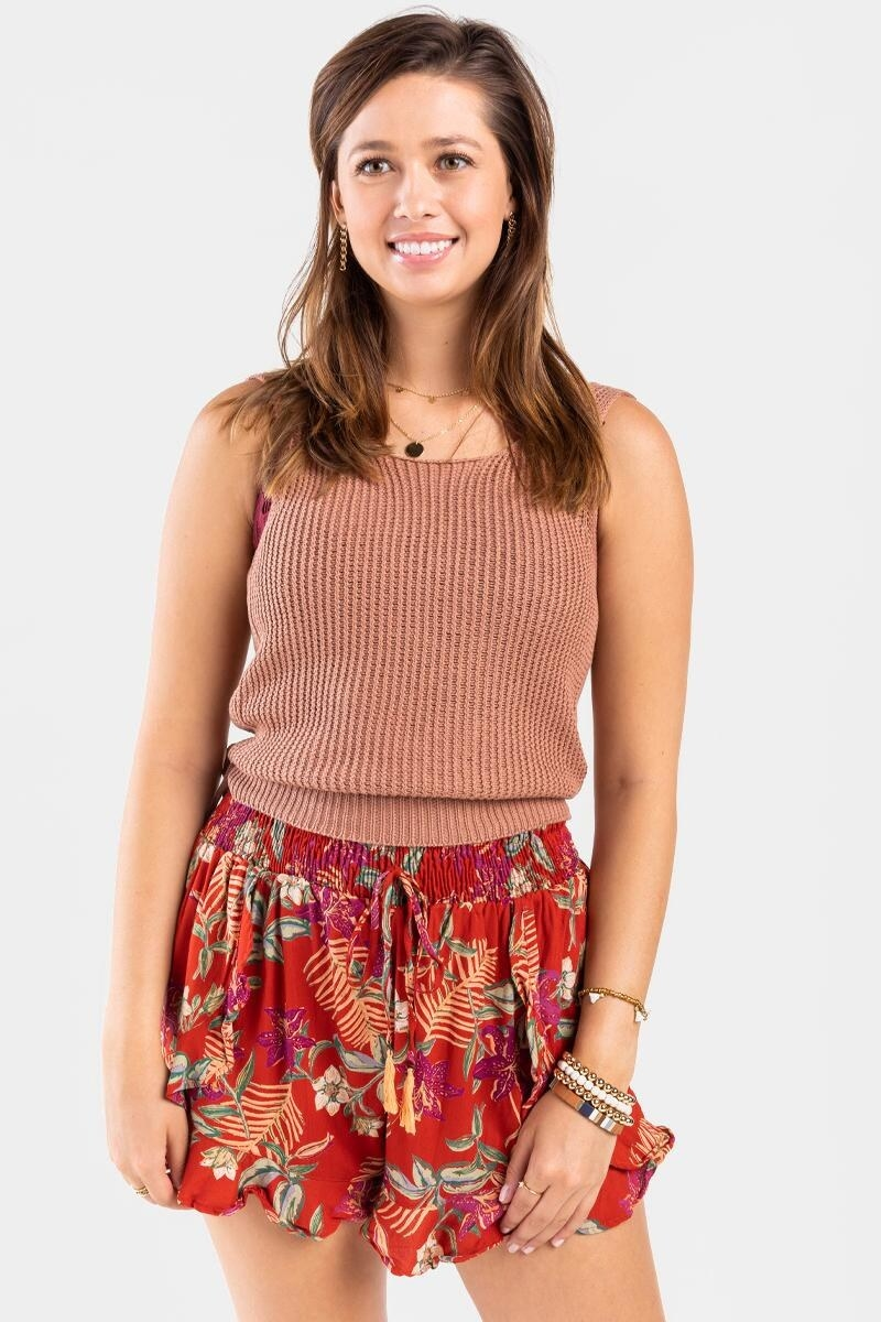 model wearing a rose tank top and red shorts with a tropical pattern, ruched waist with drawstring, and subtle ruffles on the hem