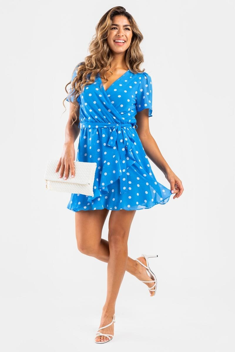 model wearing light blue dress with white polka dots, slight ruffle effect on the wrap part in front