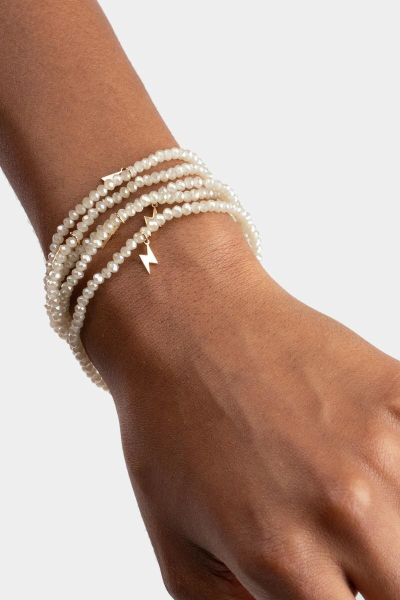 model's wrist with four strands of off white beaded bracelets with gold tone lightning bolt charms