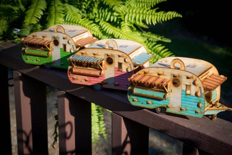 Three vintage camper birdhouses in three different colors sit on a ledge