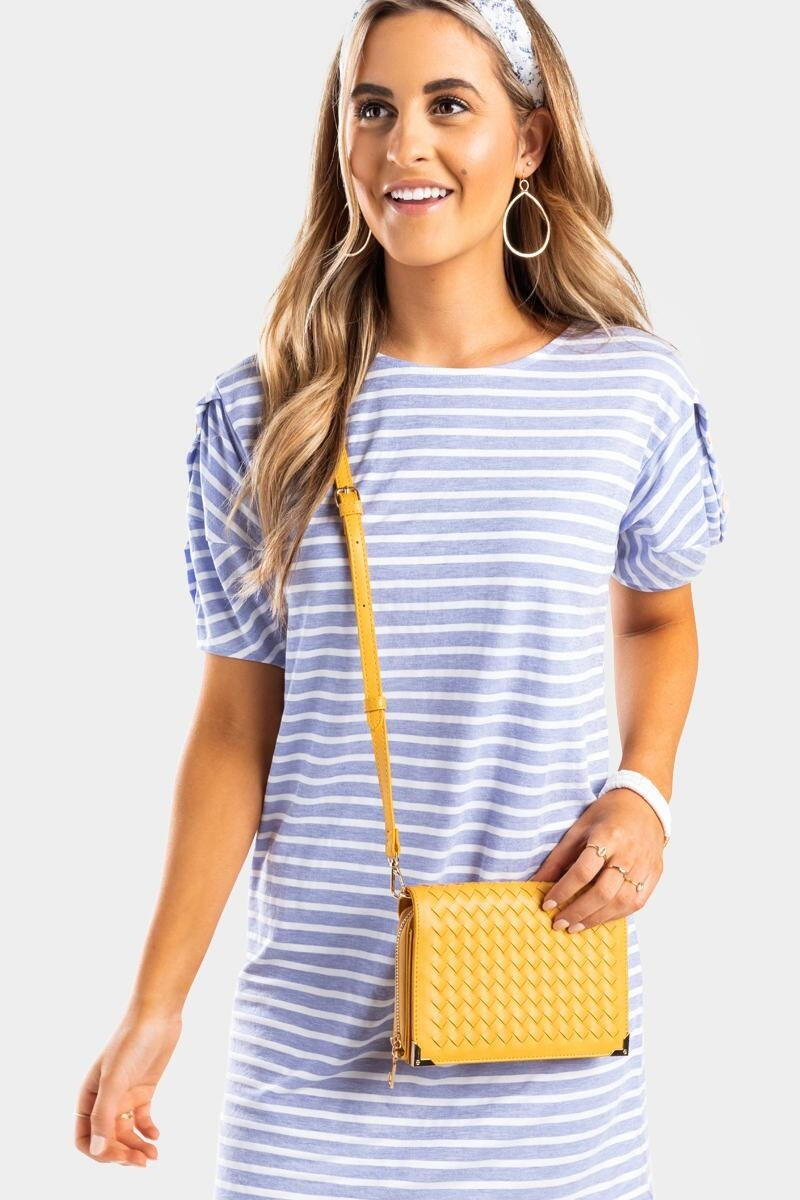 model wearing a striped dress with yellow woven-front wallet that's on a crossbody strap
