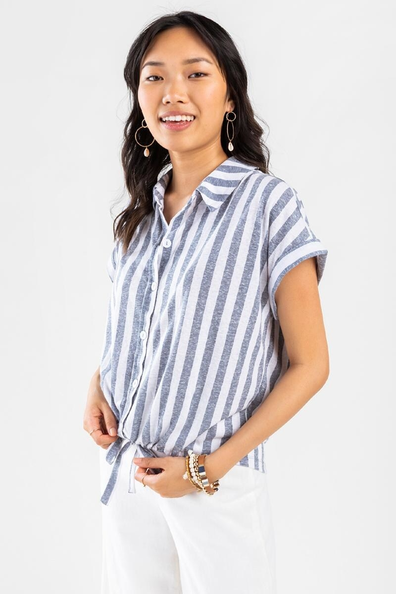 model wearing a blue and white vertical stripe sleeveless button-down shirt that ties at the waist