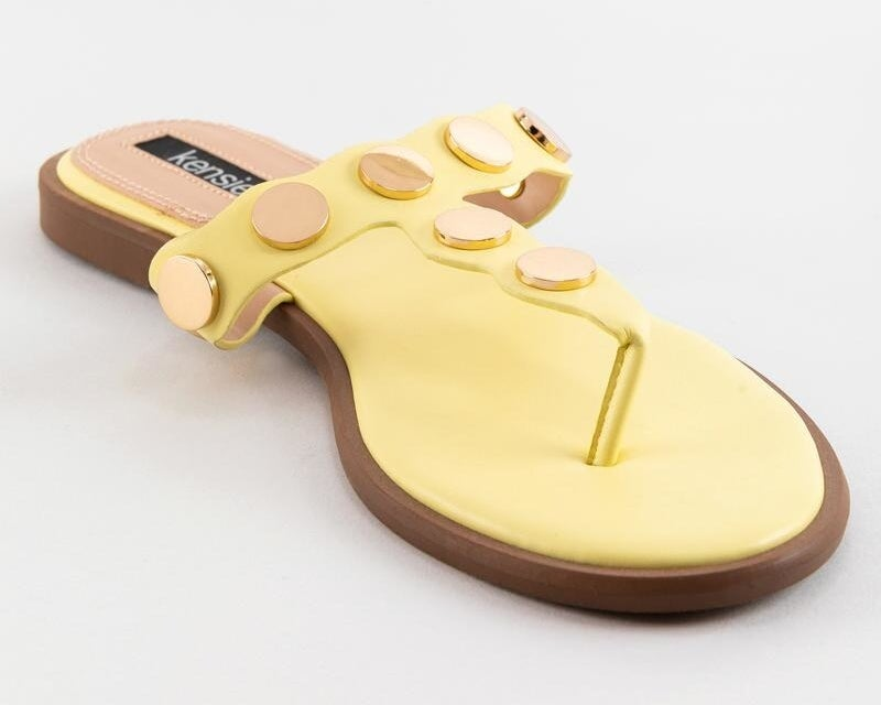 T-strap light yellow sandals with rose gold accents on the straps