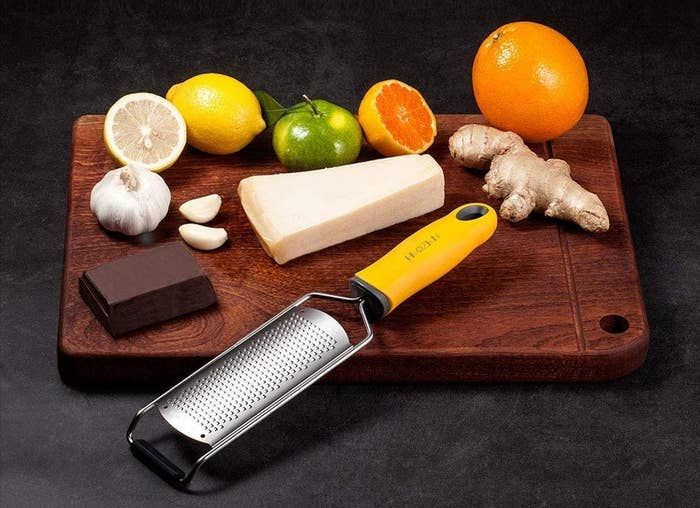 A grater is on a cutting board with cheese, chocolate, and fruit
