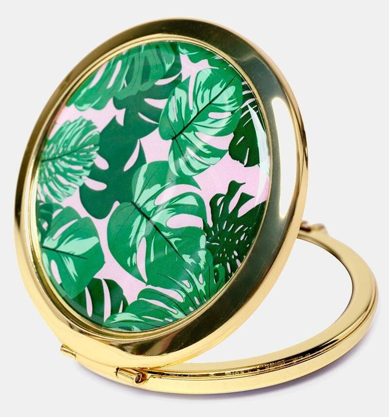 open gold tone mirror compact with top that has a palm frond print and pink background