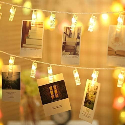 A string of clip on fairy lights with photos attached to them