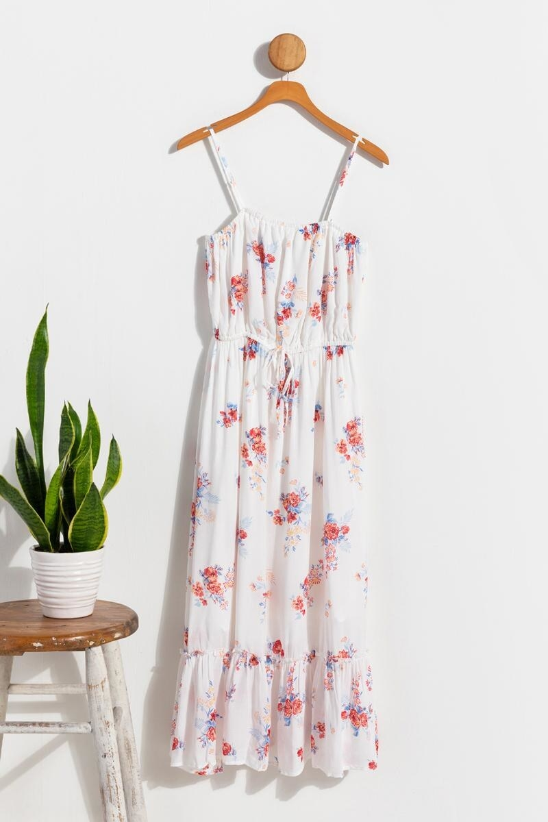 white maxi dress with pink and blue floral print, ruffles at hem, spaghetti straps hanging on a coat hanger on the wall