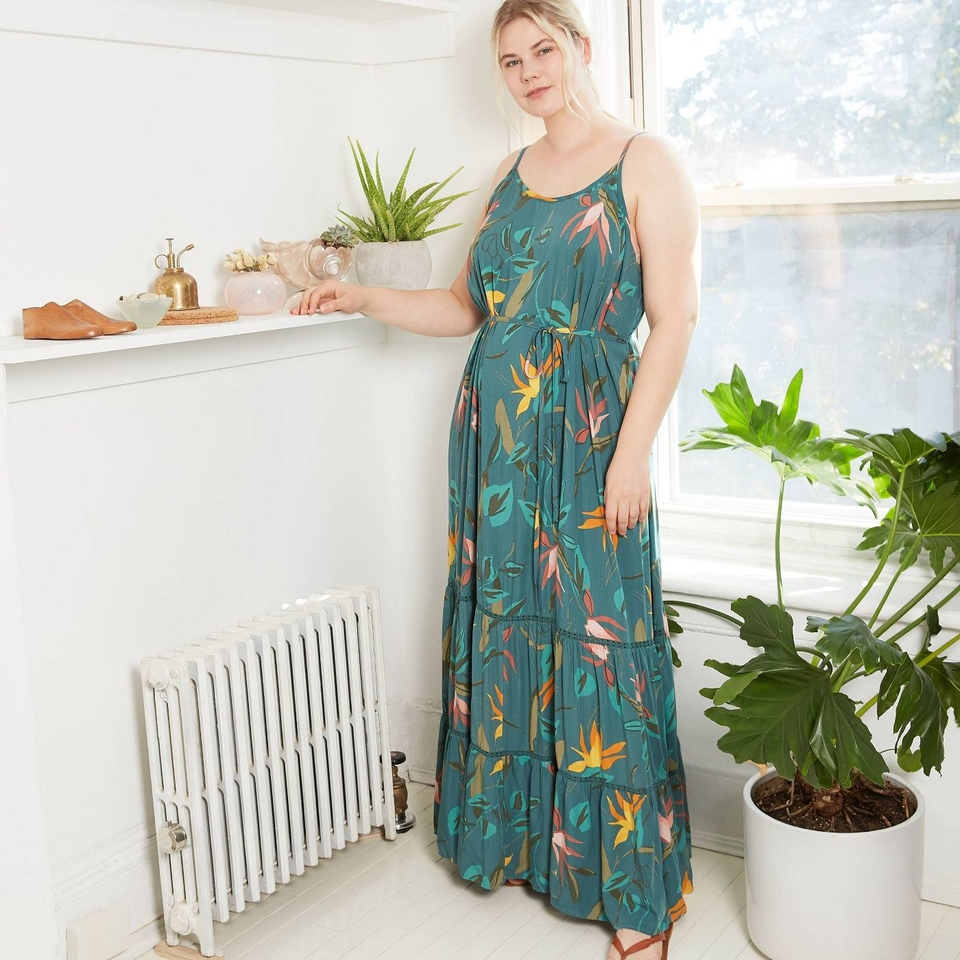A model in a tiered green strapped maxi dress with floral patterns