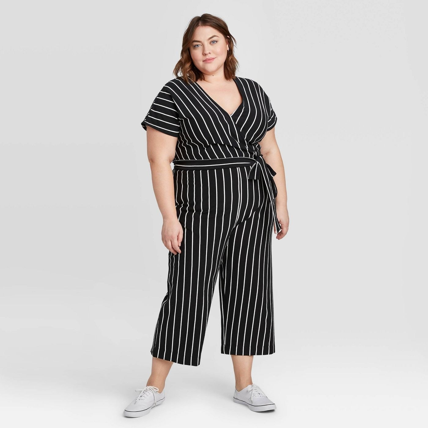 A model in a black jumpsuit with thin vertical white stripes